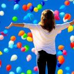 Imagen positiva de una mujer entre globos de colores