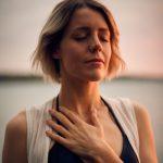 Mujer respirando produndamente con la mano en el pecho