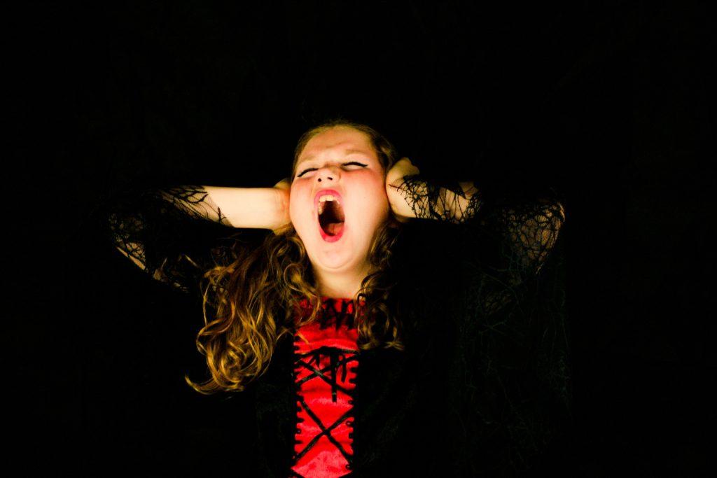 niña gritando con los oídos tapados