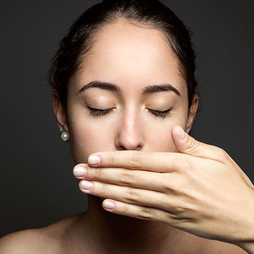 Foto de una mujer que se tapa la boca con la mano